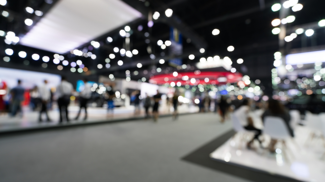 Blurred, defocused background of public event exhibition hall. Business trade show or commercial activity concept